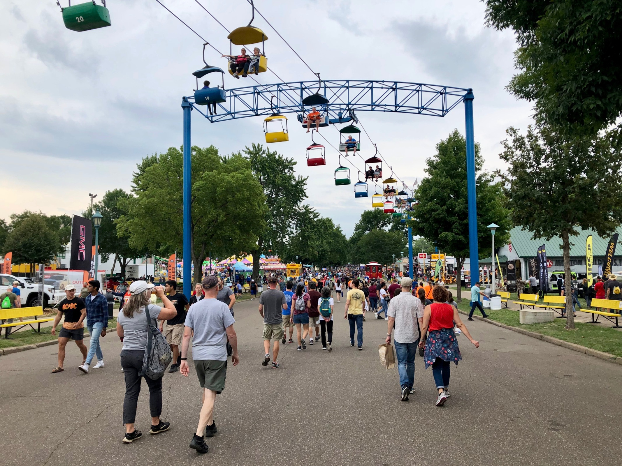 people walk below the sky ride at the state fair