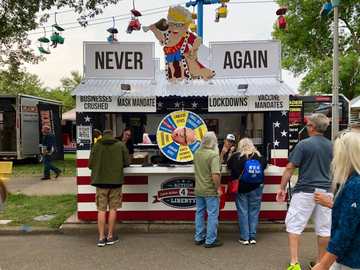 the action for america booth at the state fair, with gov. walz looking stupid and eating chicken
