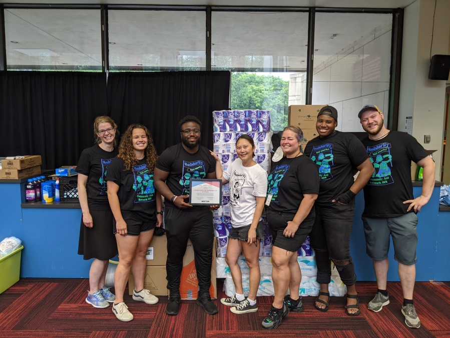 A group of CANMN lead volunteers pose with supplies for distribution