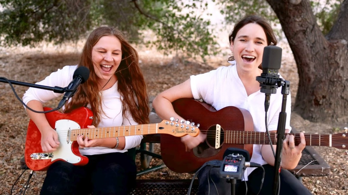 Reina Del Cid playing guitar while seated in the woods