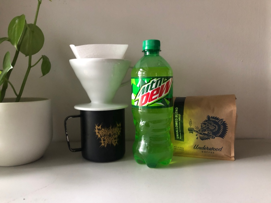A lime-green bottle of Mountain Dew next to a bag of coffee beans and a pourover and mug.