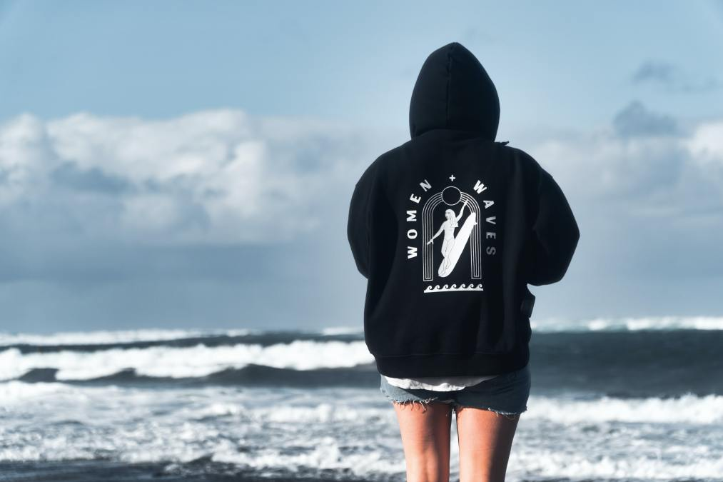 a woman standing on the shore wearing shorts and a sweatshirt