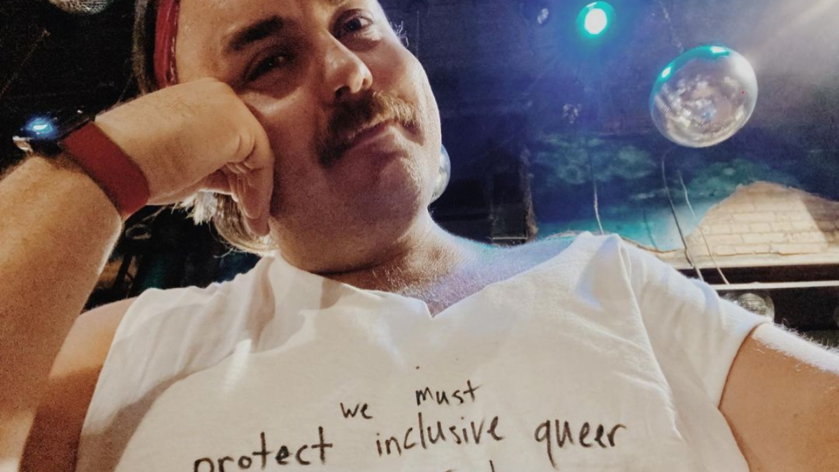 """Spencer Retelle in a T shirt reading """"w must protect inclusive queer spaces at all costs"""""""