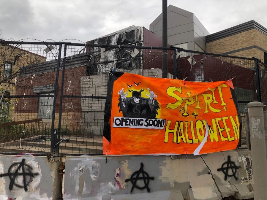 a handmade spirit halloween banner hangs outside the burnt up 3rd precinct